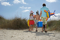 Parents and three children (6-11) carrying beach accessories back view