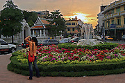 Thailand, Bangkok, tourist taking pictures of a temple at sunset