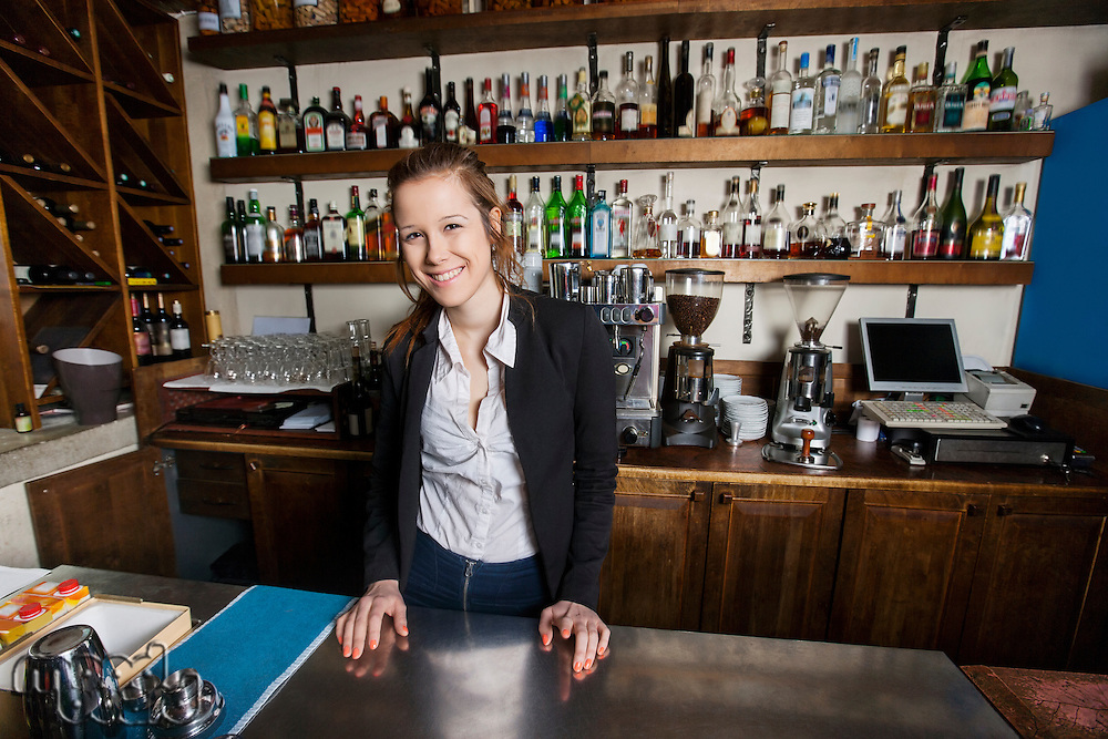 Portrait of smiling female cashier at counter in restaurant