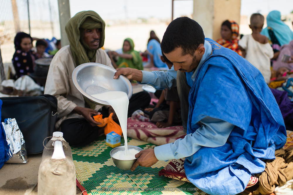 Mohamed Ag Taher preparing bowls of powdered milk for his family to drink (milk is a tuareg staple) while waiting to be registered outside the fence of a transit camp in Fassala in southeastern Mauritania on 4 March 2013. After spending the night in Fassala, they will be driven in a convoy to the main refugee camp of Mbera.