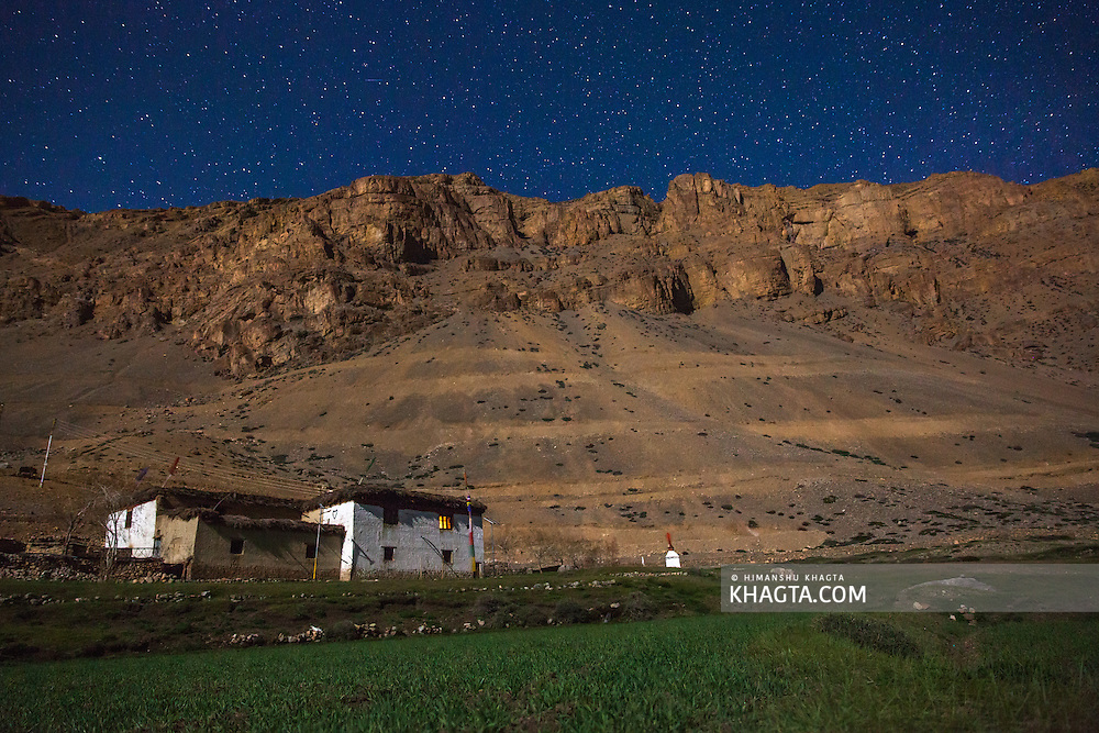 The lone house at Kakti, under the stars from a clear blue night of Spiti Valley