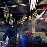 Fisherman John Pearce who uses cellar 4.<br /> Originally built to house the wares of pilchard fishermen, artists moved in to the building in the 1890's. For over 100 years the building has remained virtually untouched. The artists still coexist with the fishermen, painting in the lofts above while the fishermen mend their nets and store their fishing gear in the cellars below. Now undergoing much needed renovation, Porthmeor Artist's Studios is a microcosm of St Ives two main industries past and present.