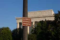 """A sign that reads """"Alcoholic Beverage Prohibited"""" on a light pole outside of the Lincoln Memorial in Washington, DC. ..The Lincoln Memorial is located on the National Mall in Washington, D.C. It is a United States Presidential memorial built to honor the 16th president of the United States, Abraham Lincoln. The architect was Henry Bacon, the sculptor was Daniel Chester French, and the painter of the interior murals was Jules Guerin...The building is in the form of a Greek Doric temple and contains a large seated sculpture of Abraham Lincoln and inscriptions of two well-known speeches by Lincoln. The memorial has been the site of many famous speeches, including Martin Luther King's """"I Have a Dream"""" speech, delivered on August 28, 1963, during the rally at the end of the March on Washington for Jobs and Freedom...Like other monuments on the National Mall, including the nearby Vietnam Veterans Memorial, Korean War Veterans Memorial, and National World War II Memorial, the Lincoln Memorial is administered by the National Park Service under its National Mall and Memorial Parks group. The National Memorial has been listed on the National Register of Historic Places since October 15, 1966. It is open to the public 24 hours a day. In 2007, it was ranked seventh on the List of America's Favorite Architecture by the American Institute of Architects."""