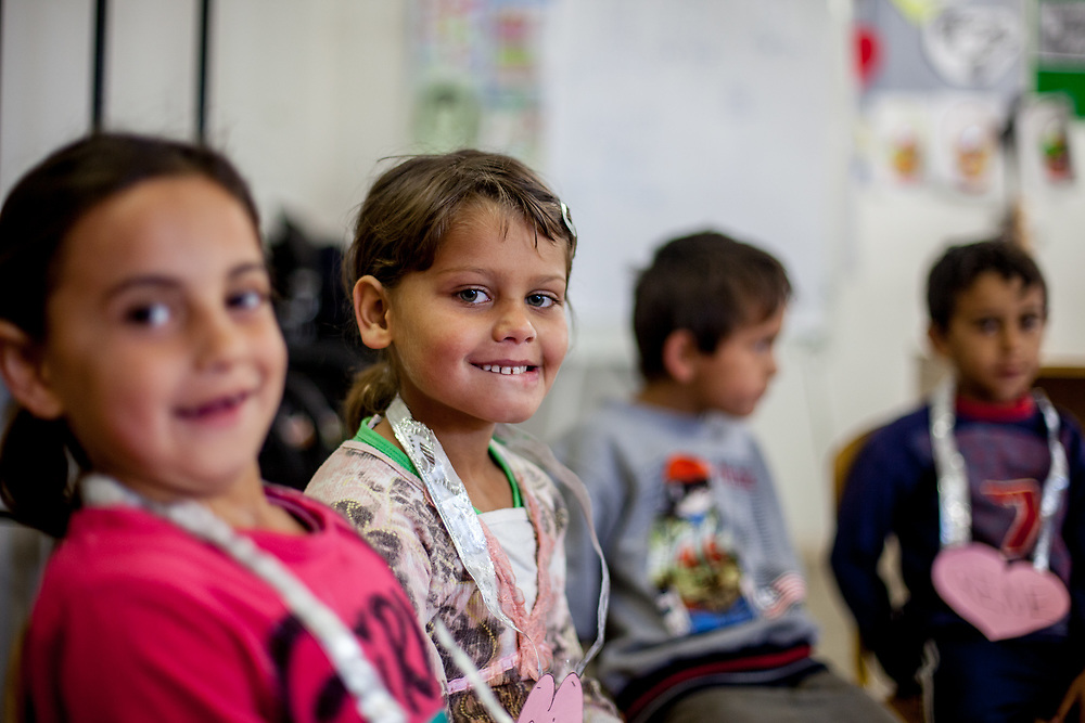 """Denisa (2nd left) and other children attend the kindergarten in the community center situated in the Roma settlement """"Budulovska Street"""" in Moldava nad Bodvou. The community center was in this time (2014) a metal, prefabricated building, which not only houses the local Roma school, but also serves as a performance space and local hangout for older Roma kids and teenagers. From about 800 inhabitants of the segregated settlement 'Budulovska Street' (2014) are roughly 392 children up to the age of 16 years."""