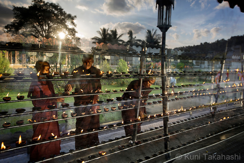 Monks light butter lamps at Sri Dalada Maligawa, or Temple of the Tooth Relic, in Srilanka on January 4, 2016. The temple houses the one of the two surviving relic of Buddha's tooth and attracts many tourists and Buddhist pilgrims. <br /> (Photo by Kuni Takahashi)