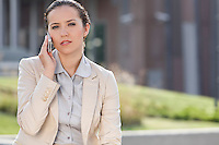 Portrait of confident young businesswoman using mobile phone outdoors