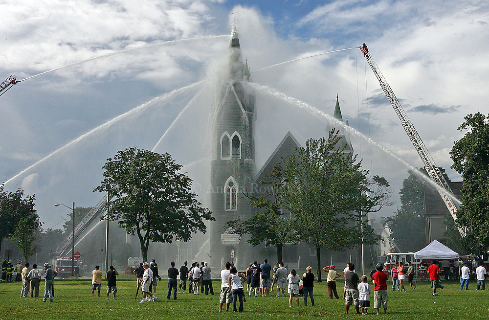 Spectators gather on Lynn Common as firefighters hose down First Baptist Church, which was struck by lightning, Sunday,  August 3, 2008.