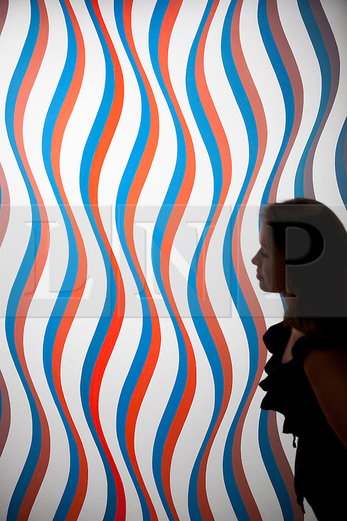 """© Licensed to London News Pictures. 03/09/2013. London, UK. A Sotheby's employee views past """"Image I, Revised White"""" (1967) by Bridget Riley during the press view for an exhibition of art from the 1960's at Sotheby's in London today (03/09/2013). The exhibition, entitled """"The New Situation: Art in London in the Sixties"""" and located at the auction house's New Bond Street building, is open to the public from 4th to the 11th of September 2013. Photo credit: Matt Cetti-Roberts/LNP"""