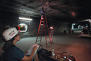 Underground storage of radioactive wastes. Measuring ceiling-floor movement. This is one of the chambers of the Waste Isolation Pilot Project (WIPP), 700 meters below ground. WIPP is a research project to determine the suitability of the local salt rocks as a storage site for highly radioactive transuranic waste from nuclear power stations. Such waste materials may have radioactive half-lives of thousands of years, and so must be isolated in a geologically stable environment. On the left is an experiment testing the design of containers carrying vitrified waste. The mine is located near Carlsbad, New Mexico, USA. (1998)