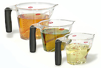 three sizes of oxo measuring cups full of varied oils