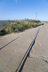 Road next to eroded railway line at Spurn Head; East Yorkshire; England,