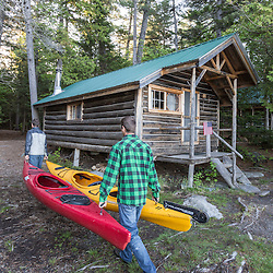 Two men carry kayaks past the cabins at the Appalachian Mountain Club's Gorman Chairback Lodge. Near Greenville, Maine.