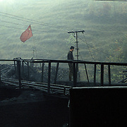 A security standing guard outside a small illegal coal mine on the Laoying mountains in China,