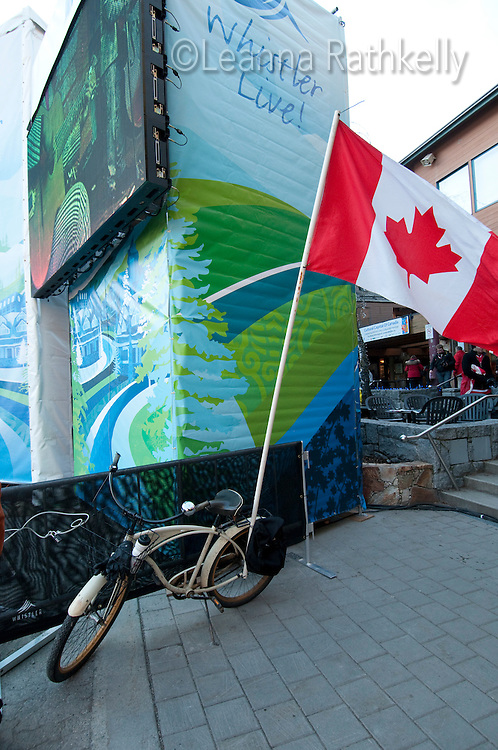 A classic bike carries a flag from Canada during the 2010 Olympic Winter Games in Whistler, BC Canada