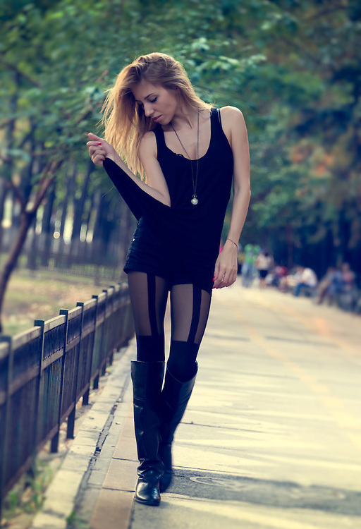 Slender fashionable woman wearing a trendy short black miniskirt and long boots walking outdoors on a sidewalk looking down