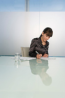Business woman writing at table in conference room