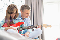 Father and daughter playing electric guitar at home