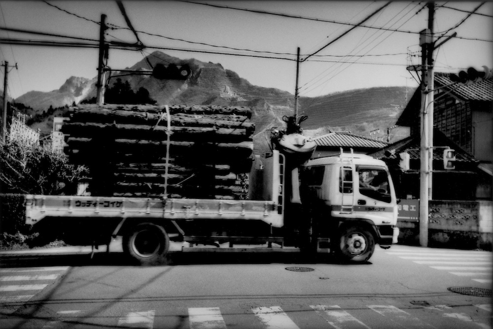 15..Logging truck in Chichibu with its strip-mined holy-mountain Mt. Buko seen in the background, Saitama Prefecture, Japan.  Traditionally the economy in the valley was based on mining, logging, agriculture and tourism from the valley's Buddhist pilgrimage.  To make ends meet, local residents often commute to the urban outskirts of the Tokyo metropolitan area.  Traditionally, Chichibu residents weathered lean times by cultivating buckwheat to make soba  noodles.  Natural resources that fueled Japan's post-war economic rise nowadays cannot compete price-wise with raw materials like stone and cement from China or timber from America's Pacific Northwest.