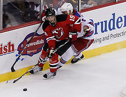 Oct 5, 2009; Newark, NJ, USA; New Jersey Devils center Travis Zajac (19) skates with the puck past New York Rangers defenseman Wade Redden (6) during the third period at the Prudential Center. The Rangers defeated the Devils 3-2.