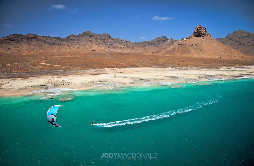 kiteboarding uninhabited desert island Santa Lucia in the Cape Verdes.  Stark contrast between green sea and baked earth with kiter in foreground