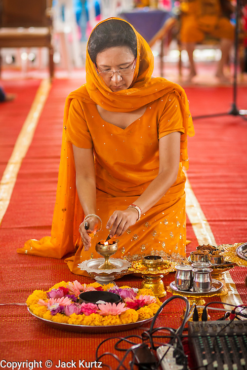 "29 SEPTEMBER 2012 - NAKORN NAYOK, THAILAND:   A woman lights an oil lamp during observances of Ganesh Ustav at Wat Utthayan Ganesh, a temple dedicated to Ganesh in Nakorn Nayok, about three hours from Bangkok. Many Thai Buddhists incorporate Hindu elements, including worship of Ganesh into their spiritual life. Ganesha Chaturthi also known as Vinayaka Chaturthi, is the Hindu festival celebrated on the day of the re-birth of Lord Ganesha, the son of Shiva and Parvati. The festival, also known as Ganeshotsav (""festival of Ganesha"") is observed in the Hindu calendar month of Bhaadrapada, starting on the the fourth day of the waxing moon. The festival lasts for 10 days, ending on the fourteenth day of the waxing moon. Outside India, it is celebrated widely in Nepal and by Hindus in the United States, Canada, Mauritius, Singapore, Thailand, Cambodia, Burma , Fiji and Trinidad & Tobago.    PHOTO BY JACK KURTZ"
