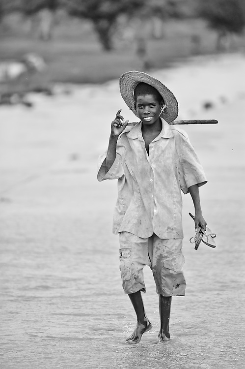 Portrait of a Burkinabe boy walking through wet season flood waters in the Sahel