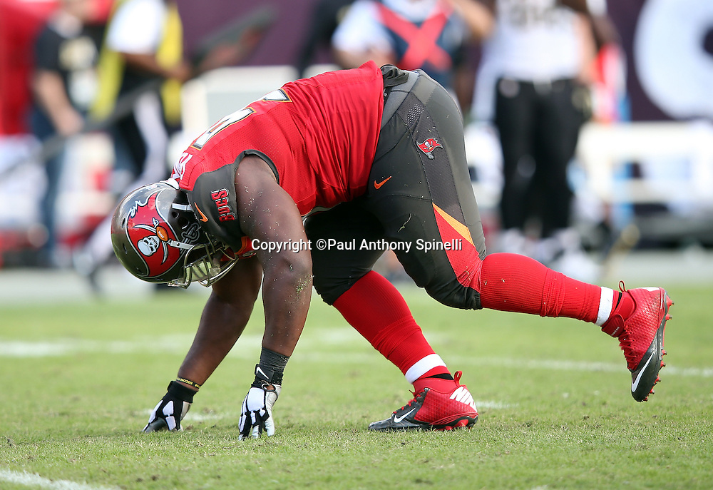 Tampa Bay Buccaneers defensive tackle Akeem Spence (97) gets up slowly after an apparent injury during the 2015 week 14 regular season NFL football game against the New Orleans Saints on Sunday, Dec. 13, 2015 in Tampa, Fla. The Saints won the game 24-17. (©Paul Anthony Spinelli)
