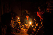 Men drink tea and play cards by the light of kerosene lamps at a roadside shop in the South 24 Parganas , West Bengal, India  Thursday, Oct. 4, 2012 (Photo/Elizabeth Dalziel for Christian Aid)