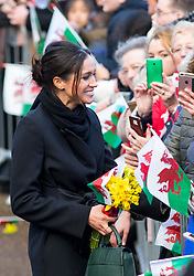 © Licensed to London News Pictures. 18/01/2018. Cardiff, UK. Meghan Markle is given a bunch of daffodils - the Welsh national symbol - as she arrives with Prince Harry (not pictured) at Cardiff Castle, to visit the Wales Culture Fair. Photo credit : Tom Nicholson/LNP
