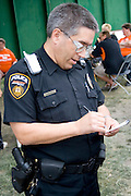 Policeman making notes. Special Olympics U of M Bierman Athletic Complex. Minneapolis Minnesota USA