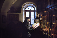 """MOUNT ATHOS, GREECE - 7 MAY 2014: Father Joachim, one of the monks living in Mylopotamos, reads and sings passages of patristic literature during the vespers (esperinos), in the cappel of the Mylopotamos skete in the Mount Athos peninsula, Greece, on May 7th 2014.<br /> <br /> The liturgical day formally begins with vespers (esperinos) which is usually sung towards the end of the afternoon. <br /> <br /> A skete is a community of Christian hermits following a monastic rule, and depending from one of the 20 monasteries ruling Mount Athos. Mylopotamos, famous for its wine and the cuisine of chef monk Father Epiphanios, is the largest dependency of the Holy Monastery of Great Lavras.<br /> <br /> Mount Athos is a mountain and peninsula in Greece. A World Heritage Site and autonomous polity in the Hellenic Republic, Athos is home to 20 stavropegial Eastern Orthodox monasteries under the direct jurisdiction of the patriarch of Constantinople. Greeks commonly refer to Mount Athos as the """"Holy Mountain"""".<br /> <br /> Mount Athos is a mountain and peninsula in Greece. A World Heritage Site and autonomous polity in the Hellenic Republic, Athos is home to 20 stavropegial Eastern Orthodox monasteries under the direct jurisdiction of the patriarch of Constantinople. Greeks commonly refer to Mount Athos as the """"Holy Mountain""""."""
