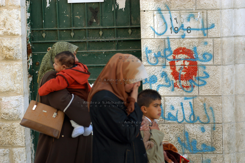 Bethlehem, Palestine 10/12/2003: mothers and sons, Ernesto Che Guevara painted on the wall - madri e figli, Ernesto Che Guevara disegnato sui muri
