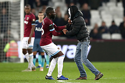 West Ham United's Arthur Masuaku (left) stops a pitch invader wearing a scream mask as he runs across the pitch during the Carabao Cup, Fourth Round match at the London Stadium.