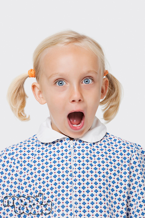 Portrait of a surprised young girl with mouth open over white background