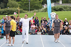 © Licensed to London News Pictures.  09/07/2012. STOKE MANDEVILLE, UK. Ian Estick, 44, from Milton Keynes leaves Stoke Mandeville Stadium, birthplace of the Paraolympics,  carrying the Olympic Torch on Day 52 of the Relay through Britain. Ian was nominated through the LOCOG public nomination for the work that he does with his charitable trust that he set up following the sudden death of his 23-month old son, Daniel. Photo credit: Cliff Hide/LNP