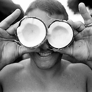A man jokes around with a fresh coconut, holding it to his eyes, on the North Shore of the island Oahu in Hawaii.