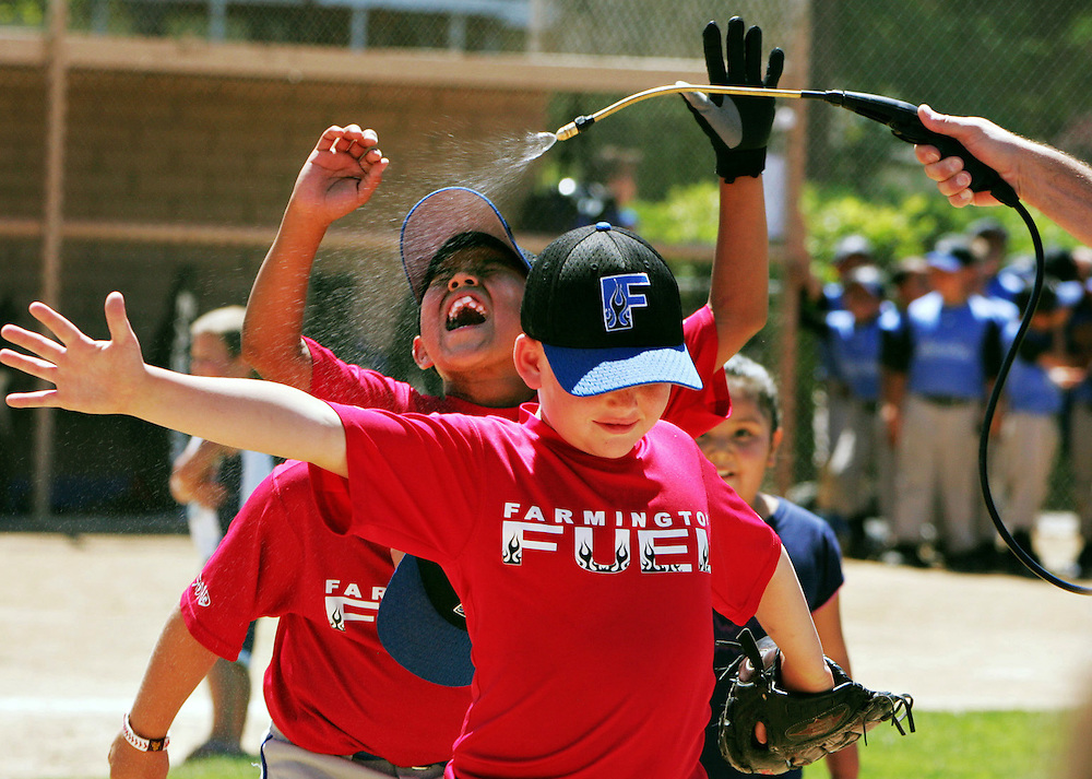 Xavier Mascareñas/The Daily Times; Farmington Fuel youth baseball players run through a cooling mist courtesy of a parent after winning the regional championship against the LumberKings at Roberto Clemente Field in Farmington, N.M., on July 11, 2009.
