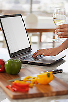 Man using lap top and chopping peppers in kitchen close up of hands