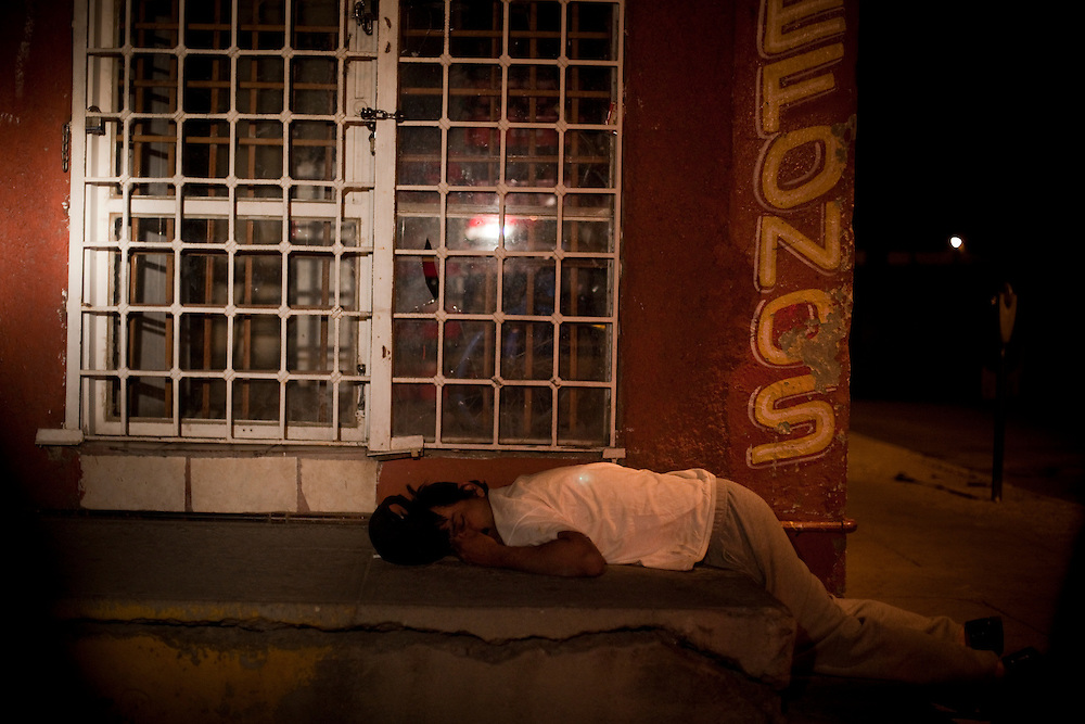 A drunk sleeps on a sidewalk in the city center of Ciudad Juarez, Chihuahua Mexico in the early hours of May 5, 2010. ..