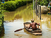 30 SEPTEMBER 2016 - SAI NOI, AYUTTHAYA, THAILAND: A person paddles home in the flooded Sai Noi. The Chao Phraya River, the largest river that runs through central Thailand, has hit flood stage in several areas in Ayutthaya and Ang Thong provinces. Villages along the river are flooded and farms are losing their crops due to the flood. This is the same area that was devastated by floods in 2011, but the floods this year are not expected to be as severe. The floods are being fed by water released from upstream dams. The water is being released to make room for heavy rains expected in October.      PHOTO BY JACK KURTZ