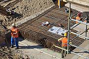 Nederland, Nijmegen, 12-3-2015 Aan de overkant van de Waal bij Lent wordt druk gewerkt aan het creeren van een nevengeul in de rivier om bij hoogwater een betere waterafvoer te hebben. Het is een omvangrijk project waarbij onder meer de pijlers van het spoorviaduct een bredere basis moeten krijgen omdat die straks in de loop van het water staan. Ook de n325 die vanaf de Waalbrug naar Arnhem loopt moet over 400 meter opnieuw worden aangelegd omdat het talud vervangen wordt door pijlers (foto). De weg wordt via een bypass omgeleid. Het dorp veurlent komt op een kunstmatig eiland te liggen met twee bruggen als ontsluiting. Een voetgangersbrug en de andere voor normaal verkeer. Inmiddels begint de nieuwe kade aan de noordkant van deze geul vorm te krijgen. Ruimte voor de rivier, water, waal. In de nieuwe dijk wordt een drempel gebouwd die stapsgewijs water doorlaat en bij hoogwater overloopt. Measures taken by Nijmegen to give the river Waal, Rhine, more space to flow during highwater and to prevent the risk of flooding. Room for the river. Reducing the level, waterlevel. Foto: Flip Franssen/Hollandse Hoogte