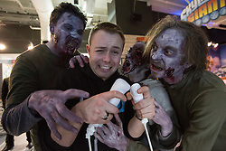 © licensed to London News Pictures. London, UK 29/11/2012. A new Nintendo Wii U owner surrounded by zombie lookalikes at the launch of Nintendo's latest gaming console at HMV Store in Oxford Street, London. Photo credit: Tolga Akmen/LNP