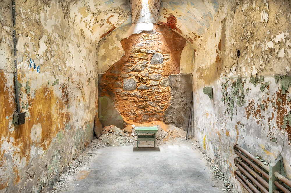 Chair in empty prison cell with falking wals and skylight above, Eastern State Penitentiary, Philadelphia, PA.