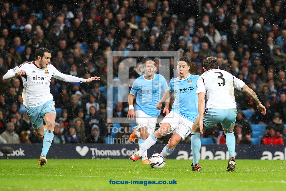 Picture by Paul Chesterton/Focus Images Ltd +44 7904 640267<br /> 08/01/2014<br /> Samir Nasri of Man City takes on George McCartney of West Ham during the Capital One Cup Semi Final 1st Leg match at the Etihad Stadium, Manchester.