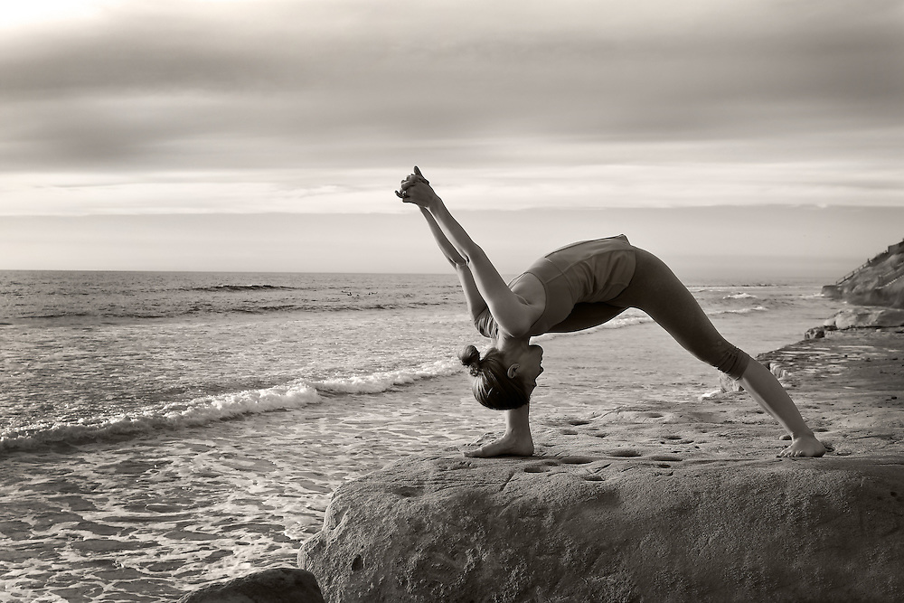 Woman doing pilates and yoga on the rocks at Terramar Cliffs in Carlsbad, CA.