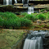 A clear stream cascades down layered beds of sandstone amidst lowland rainforest. Sarawak, Malaysia.