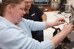 Woman with a mild learning disability working as a trainee computer technician, shown here attaching hard drive, helped into employment by the Ready 4 Work team, Nottinghamshire County Council, with trainer