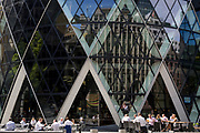Afternoon drinkers enjoy warm summer sunshine beneath the architecture of the Swiss Re building (aka The Gherkin), on 17th Juy 2017, in the City of London, England.