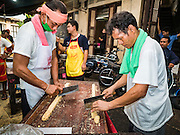 04 OCTOBER 2016 - BANGKOK, THAILAND:  Men make Chinese peanut brittle at the Vegetarian Festival at the Chit Sia Ma Chinese shrine in Bangkok. The Vegetarian Festival is celebrated throughout Thailand. It is the Thai version of the The Nine Emperor Gods Festival, a nine-day Taoist celebration beginning on the eve of 9th lunar month of the Chinese calendar. During a period of nine days, those who are participating in the festival dress all in white and abstain from eating meat, poultry, seafood, and dairy products. Vendors and proprietors of restaurants indicate that vegetarian food is for sale by putting a yellow flag out with Thai characters for meatless written on it in red.    PHOTO BY JACK KURTZ