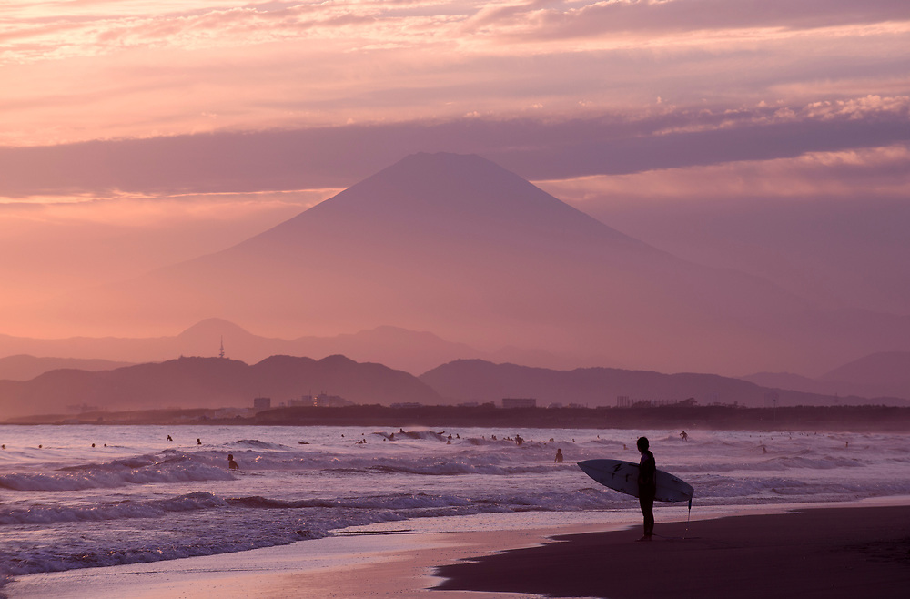 A surfer stands on the beach at sunset, with Mt. Fuji in the background, in Fujisawa City, Kanagawa Prefecture, Japan.